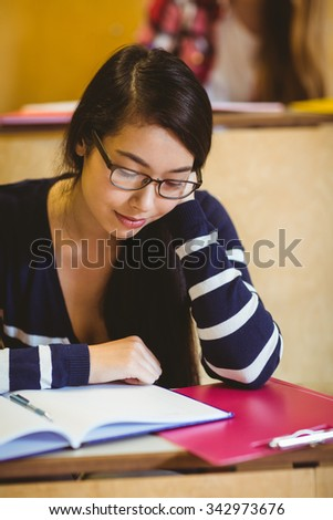 Focused student reading on notebook at the university - stock photo