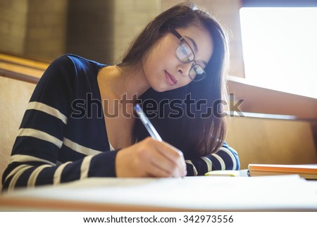 Focused student writing on notebook at the university - stock photo