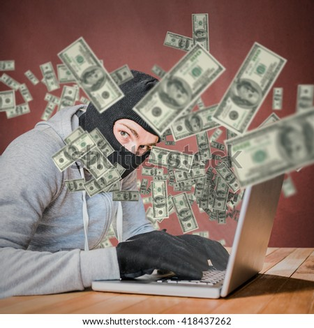 Focused thief with hood typing on laptop against orange