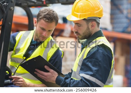 Focused warehouse workers talking together in warehouse - stock photo