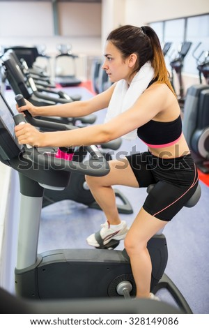 Focused woman using the exercise bike at the gym - stock photo