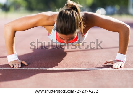 Focused young beautiful woman doing push-ups outdoors on a hot summer day