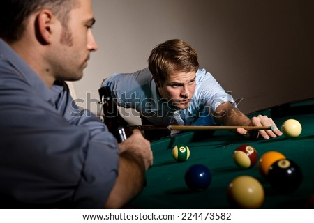 Focused young casual caucasian man playing billiard with friend. Holding cue ready to strike the ball. Concentration, game. - stock photo