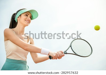 Focused young female tennis player on tennis court. - stock photo