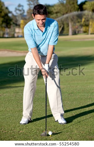 Focused young man at the course playing golf - stock photo
