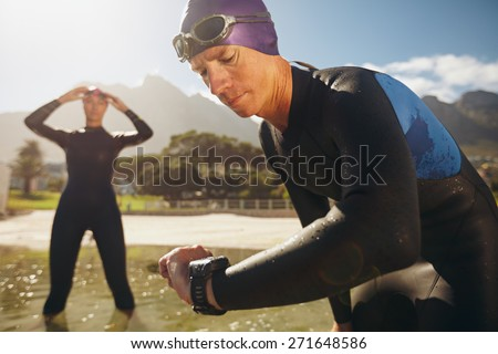 Focused young man checking his watch while in wetsuit at the lake. Man looking at watch after practice run. Triathletes getting ready for race. - stock photo