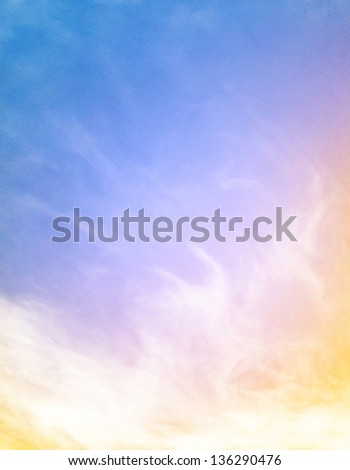 Fog and clouds on a colorful blue to orange gradient.  Image displays a pleasing paper grain and texture at 100%. - stock photo