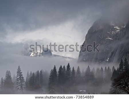 fog and low clouds rolling in yosemite valley on a cold winter morning,with snow covering the grounds. - stock photo