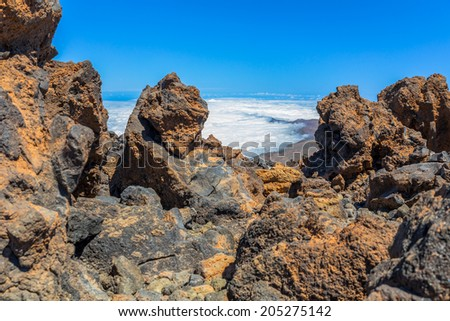 Fog bank in a valley behind volvanic rocks from Teide volcano. - stock photo