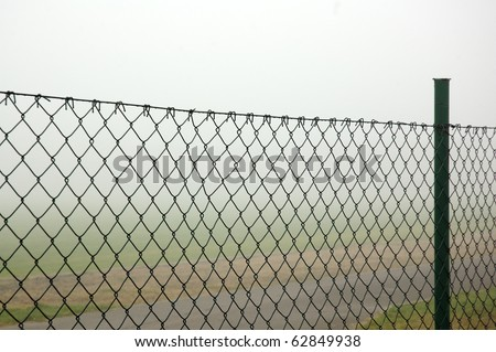 Fog behind the wire fence - stock photo