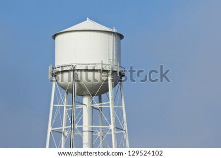 Fog clears revealing a white water tower.