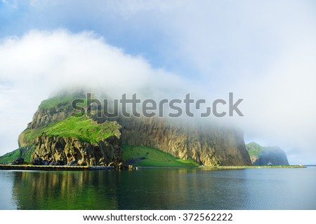 Fog covered green island