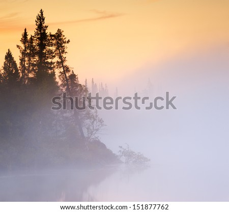Fog creeps over the water on the lake - stock photo