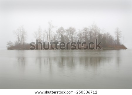 Fog Island. Calm water surrounds an island during a foggy day in the Pacific Northwest.  - stock photo