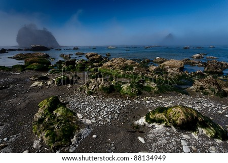 Fog lifts on a rocky beach with and offshore islands - stock photo
