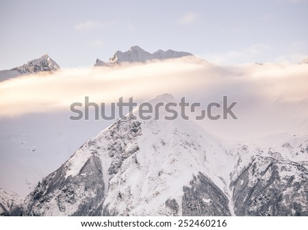 Fog over Alaskan mountain peaks at sunset. - stock photo