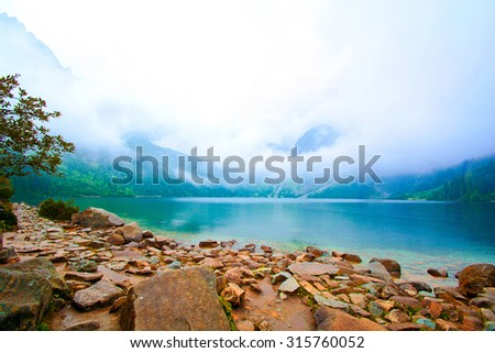 Fog over lake in mountains. Fantasy and colorful nature landscape. Nature conceptual image. Morskie Oko in Tatry, Poland. - stock photo