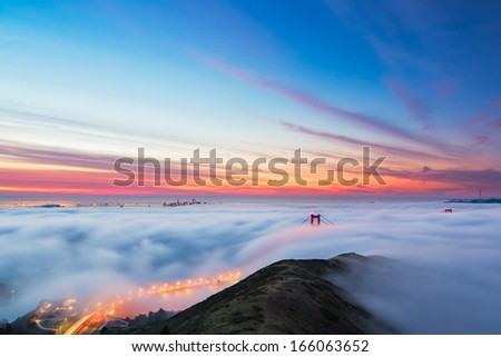 Fog pours into the bay and over the Golden Gate Bridge as sunrise lights the clouds over San Francisco, California.  - stock photo