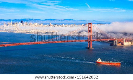 Fog rolling over Golden Gate Bridge and San Francisco on a late summer afternoon. - stock photo