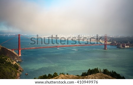 Fog rolls over the Golden Gate Bridge and San Francisco skyline on a summer day in July 2014. - stock photo