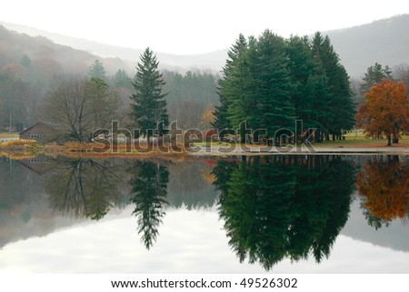 foggy forest and hills beside a lake - stock photo
