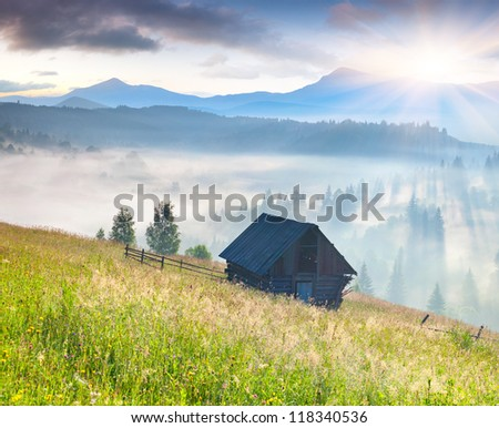 foggy landscape with an old barn in the mountains at the summer - stock photo