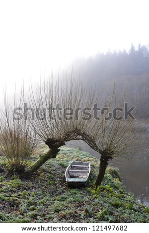 Foggy morning - boat under willow trees on the shore of Lu�¾nice river in Czech Republic. - stock photo