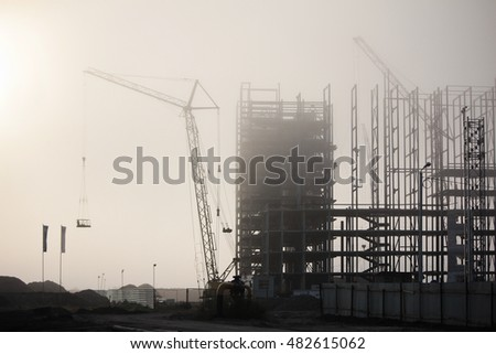 foggy morning. fog on the high-rise construction site frame building. crane boom hidden in the fog