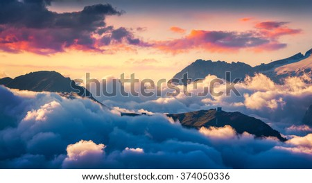 Foggy morning scene in the Val di Fassa valley. View from the bird's eye from Sella pass, Province of Bolzano - South Tyrol. Sunrise in Dolomite Alps, Italy, Europe. - stock photo