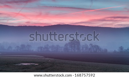 Foggy Morning Sunrise in Bavaria. Clear Sky. Hills and Forest. Barren trees and old grass. Beautiful rural landscape