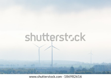 Foggy morning with wind power plants in the landscape - stock photo