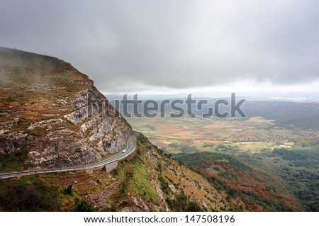 foggy mountain pass with a road and a car climbing - stock photo
