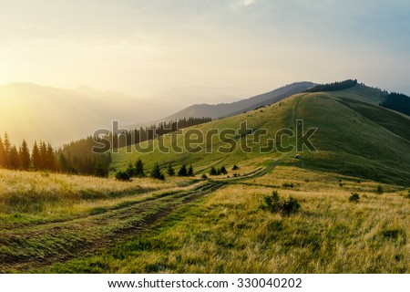 Foggy mountain road goes on top of the hills on sunset landscape. Sunbeams through the trees. - stock photo