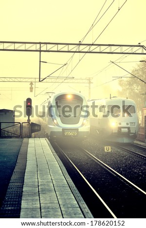 Foggy railroad station in first morning light - stock photo