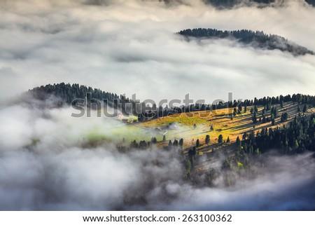Foggy summer sunrise in the Italian Alps. Ferchetta mountain range, Dolomites mountains, Italy, Europe. - stock photo