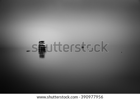 Foggy sunrise at Panorama Point in Vancouver, BC featuring a calm ocean with sunrise reflections on the smooth water - stock photo