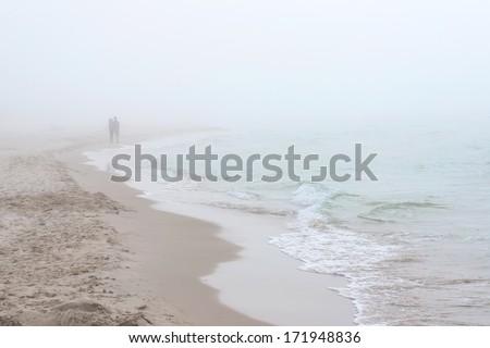 Foggy weather by the sea. Baltic beach in Leba, Poland. Couple walking along coastline. Baltic beach in Leba, Poland.  - stock photo
