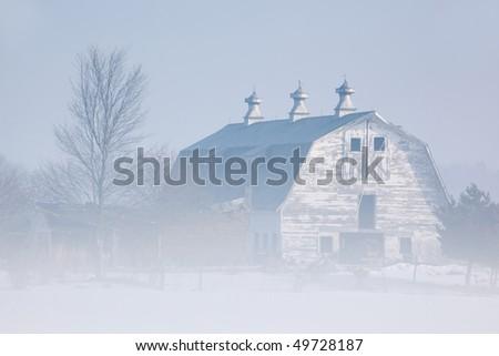 Foggy winter landscape of white barn, Michigan, USA - stock photo