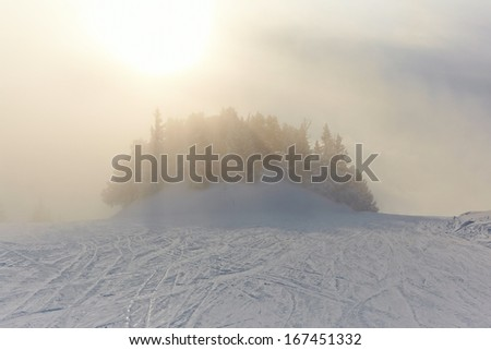 Foggy winter landscape with skiing slope - stock photo