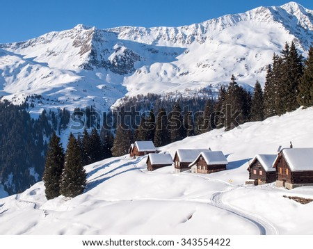 Foisch, Switzerland: Snowy mountain chalet in wood and illuminated by the sun create a aplendido winter scenery and characteristic of the Swiss Alps. - stock photo