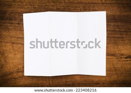Fold paper on wood background - stock photo