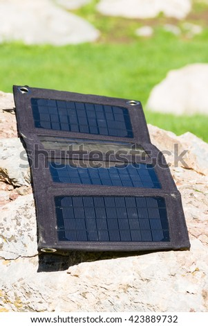 Foldable solar panel in a mountain base camp - stock photo