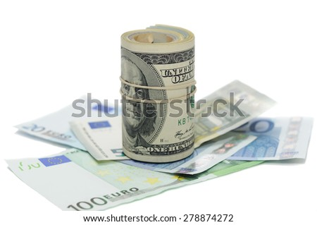 Folded bills wrapped by rubber lying over banknotes - stock photo