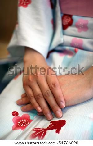 Folded hands over a Japanese flower kimono - stock photo