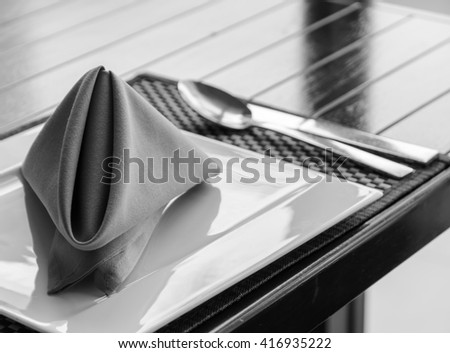 Folded napkin on white plate, table setting in black and white image - stock photo