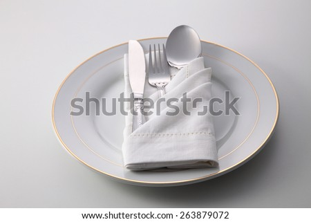 Folded napkin with fork, spoon and knife, on plate - stock photo
