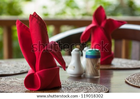 Folded napkins outdoors on a table in the tropics - stock photo