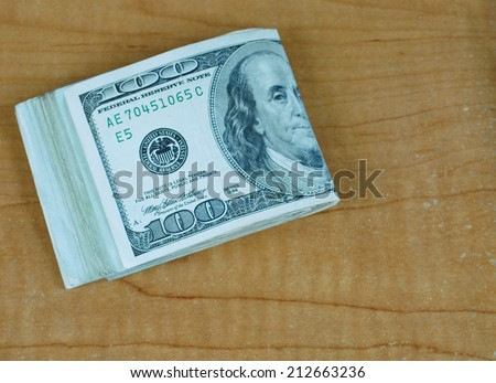 Folded stack of many US one hundred dollar bills shot from above on scratched and worn desk with copy space. Good for any fiscal, finance, currency, market, investment or budget concept - stock photo