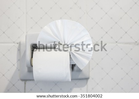 folded toilet paper on the wall with a toilet paper holder - stock photo