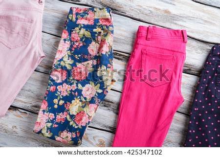 Folded trousers of different color. Trendy pants on wooden background. Selection of merchandise on shelf. Buy one and get two. - stock photo